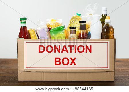 Various Food Items In Donation Box On Wooden Table