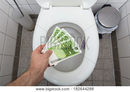 Elevated View Of A Man's Hand Throwing Hundred Euro Notes In Toilet