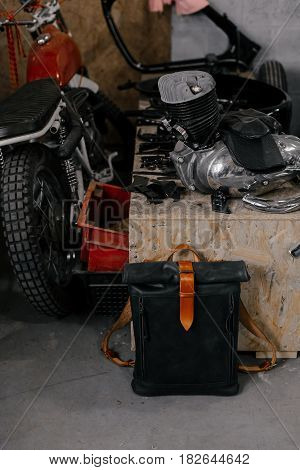 Exclusive black leather backpack. Backpack near the wall. The tools in the garage. Many different tools. Motorcycle in the garage. Garage