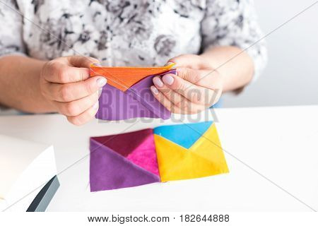 needlework and quilting workshop of a tailor woman on white background - close-up on hands of a woman tailor collect drawing of colorful fabrics for patchwork