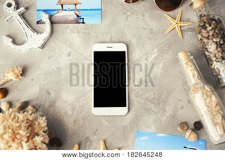 Composition with smart phone on gray textured background. Travel apps concept