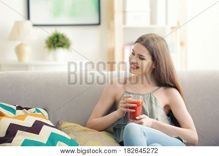 Young woman tasting fresh juice sitting on couch at living room