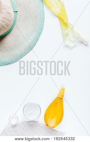 Sun protection concept with cream and lotion and summer accessories, hat on white background top view mockup