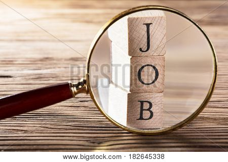 Close-up Of Job Block Seen Through Magnifying Glass On Wooden Table