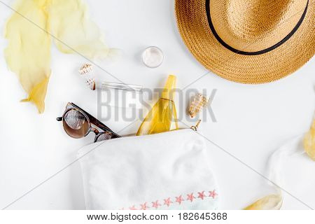 Sun protection concept with cream and lotion and summer accessories, hat and sunglasses on white background top view