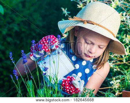 Cute Girl Watering Herbs. Child Taking Care Of Plants. Kid With Water Can. Little Gardener With Lave