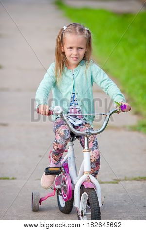 Adorable girl riding a bike on beautiful summer day