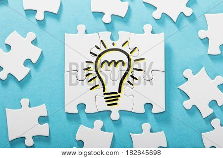 Elevated View Of Light Bulb Icon On White Puzzle Over The Blue Background