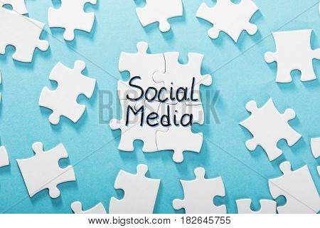 Elevated View Of Social Media Word Made With Puzzle Over The Blue Background