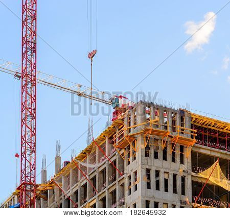 Crane on the construction of an office building against blue sky with clouds