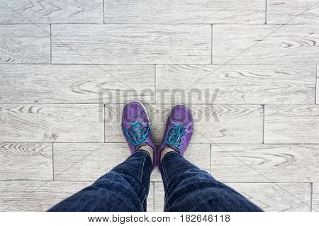 Feet concept with purple shoes on wood stone background