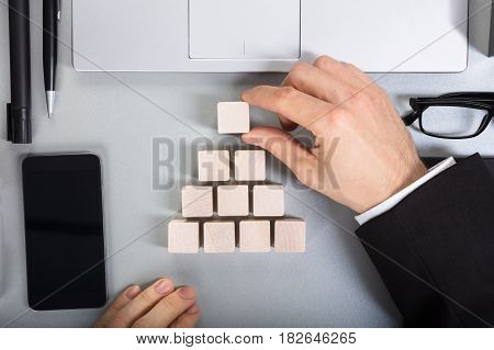 Close-up Of A Businessperson Arranging Wooden Block On Office Desk