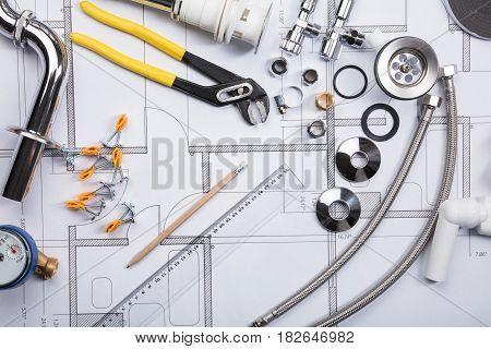 High Angle View Of Various Plumbing Fixtures On Blueprint
