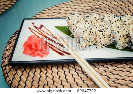 A plate with delicious rolls ginger and chopsticks