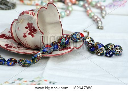 Antique blue bead necklace spilling from antique teacup