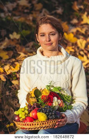 A woman sitting on the ground covered with autumn leaves and holding autumn basket with fruits and flowers