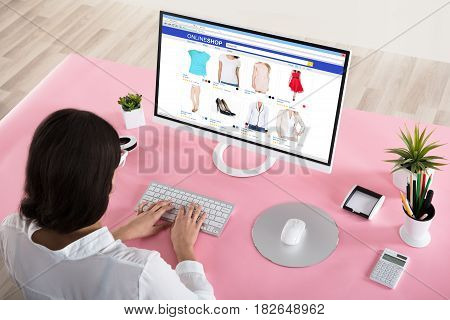 Rear View Of A Businesswoman Shopping Online With Pink Desk In Office