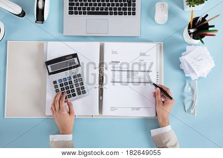 Elevated View Of A Businesswoman Calculating Invoices Using Calculator On Desk
