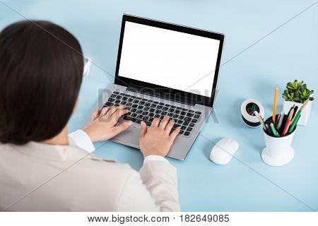 Rear View Of A Businesswoman Using Laptop On Blue Desk In Office