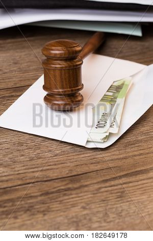 Envelope with money and hammer