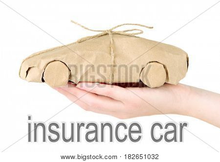 Car insurance concept. Woman holding automobile wrapped in paper on white background