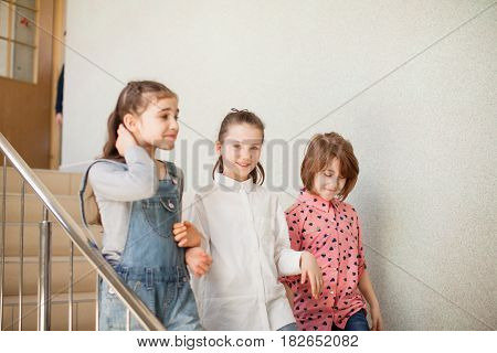 Three girls in the school hallway talking resting during the break