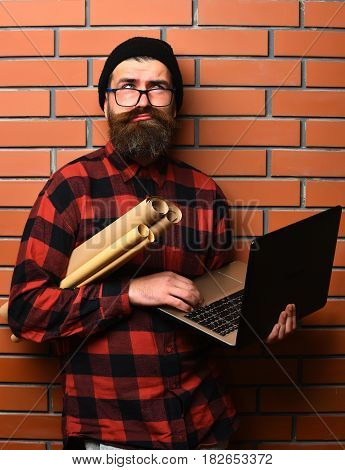 Bearded Brutal Caucasian Hipster Holding Laptop And Craft Paper