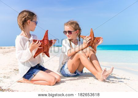 Adorable little girls with starfish on the beach