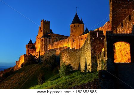 Ancient Walled City Of Carcassonne, France, Lit In The Early Night