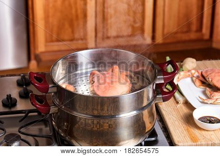 Large cooked crab in hot steaming pot with kitchen counter and serving board in background. Selective focus on front of crab