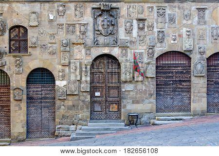Coats of arms and heavy doors on the facade of Palazzo Pretorio - Arezzo, Italy
