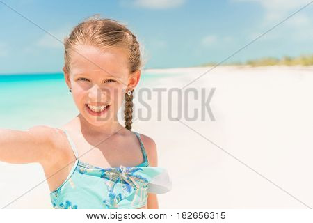 Little girl taking selfie portrait with her smartphone on the beach
