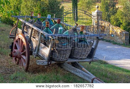 An old cart with demijohns in front of an iron gate - Montalcino, Italy