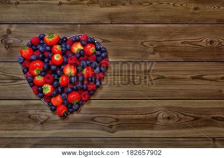 Colorful heart shape made using various berries including strawberries raspberries and blue berries on a wooden background with space for text. Can be used as a background for Valentines or Mothers Day.
