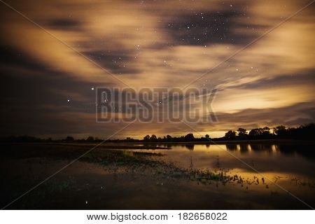 Beautiful night starry landscape. Stars in sky reflected in the water. Astrophotography. Clear starry sky. Slow shutter speed. The spectacular sky. Night sky. Starry sky. Dark sky. Stars in morning sky