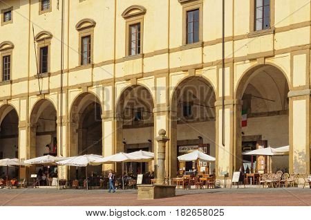 Cafes and restaurants under the yellow facade and elegant arches of Loggia del Vasari - Arezzo, Italy, 24 September 2011