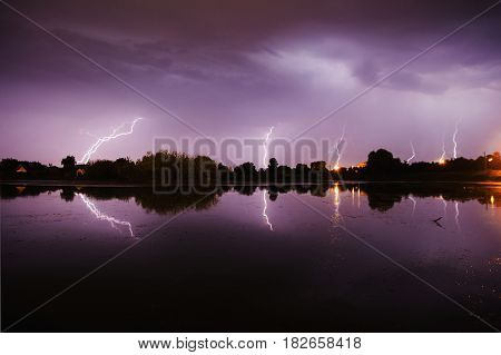 Bolts of lightning in sky over the river. Thunder Sky with lightning. The beautiful night scenery with lightning in sky. Slow shutter speed. The spectacular sky. Scenic view with sky. The surface of the water with lightning in sky. Night sky. Storm in sky