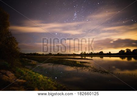 Beautiful night starry landscape. Stars reflected in the water. Astrophotography. Clear starry sky landscape. Slow shutter speed. Landscape with the spectacular starry sky. Scenic starry view. Starry landscape