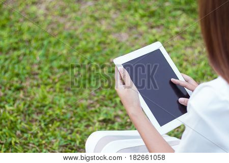 Woman using Hands touching on a blank screen on modern tablet phone screen