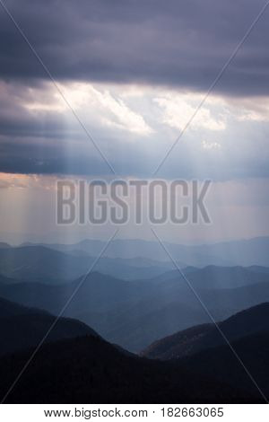 The sun rays shine down over the peaks and ridges of the Blue Ridge Mountains