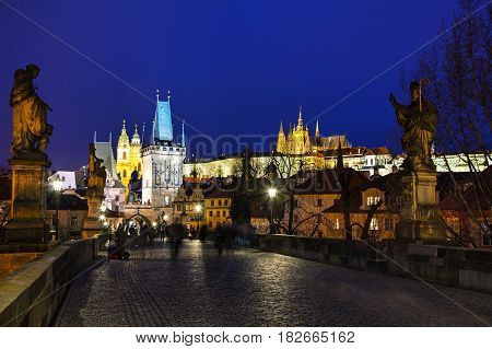 PRAGUE - MARCH 03: Charles bridge in the evening with people on March 03 2017 in Prague. This famous historic bridge crosses the Vltava river and was constructed in the beginning of the 15th century.
