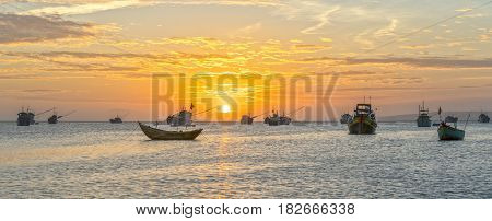 Mui Ne, Vietnam - February 18th, 2017: Sunset at Fishing village and traditional Vietnamese fishing boats with hundreds of boats moored in a line beautifully in Mui Ne, Vietnam