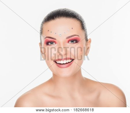 Prtrait of beautiful woman with bright make-up and crystals on face