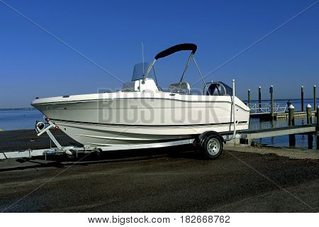 Boat on trailer performing maneuvers of landing near a pier