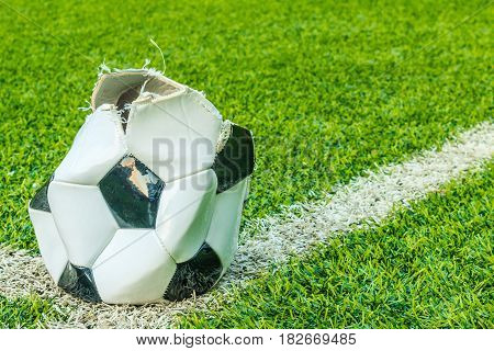 Dilapidated soccer ball in the artificial turf