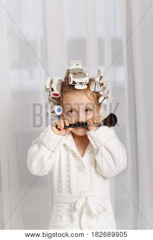 Little girl fashionista. Girl in curlers and a robe holding a makeup brush. Little coquette fooling around. Human emotions. She made a mustache out of her brush.