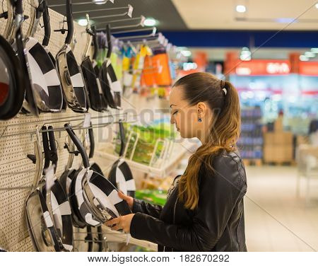 woman housewife chooses frying pan in the supermarket. She is holding one pan
