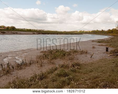 A Waterway River Through The Uk With Low Tide And Birds Wading In The Water And The Mud Bank With A