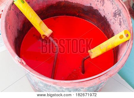 Plastic bucket with red paint before painting and paint rollers with yellow handles are in apartment during under renovation remodeling and construction of apartment.