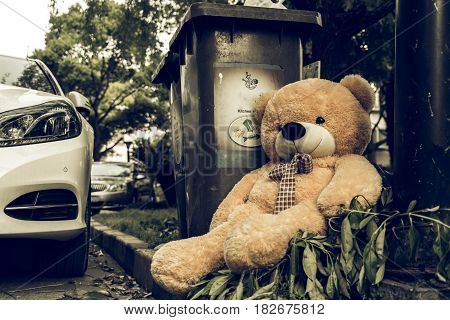 The teddy-bear was throw away sitting beside the garbage trash
